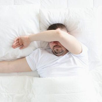 man sleeping on a bed with his arms covering his eyes