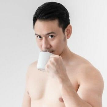 shirtless man sipping coffee