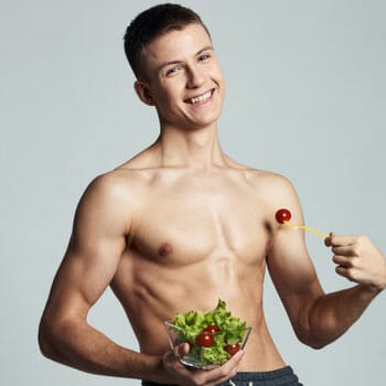 shirtless man holding up a bowl filled with salad