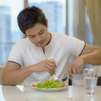 man seated in a kitchen table eating