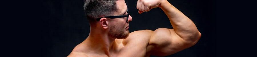 shirtless man showing off his left arm biceps