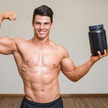 shirtless man raising up a supplement container and flexing his biceps