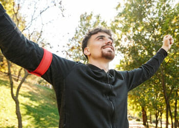 man raising his arms in happiness outdoors