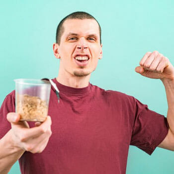 man flexing his biceps and raising a cup of food