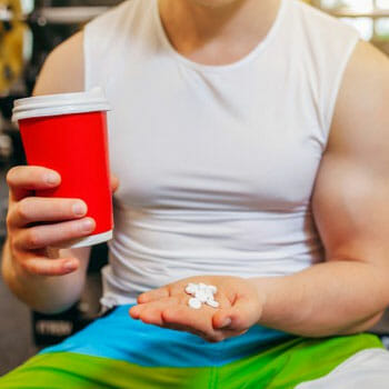 man in a gym holding a drink in one hand and holding a stack of pills on the other
