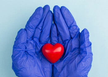 hands in surgical gloves holding a small heart toy