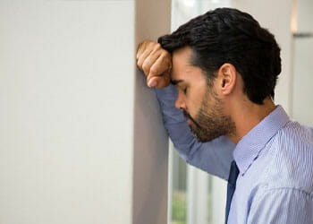 man worrying while leaning towards a wall