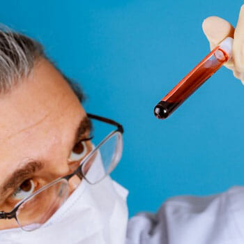 medical person holding up a blood sample