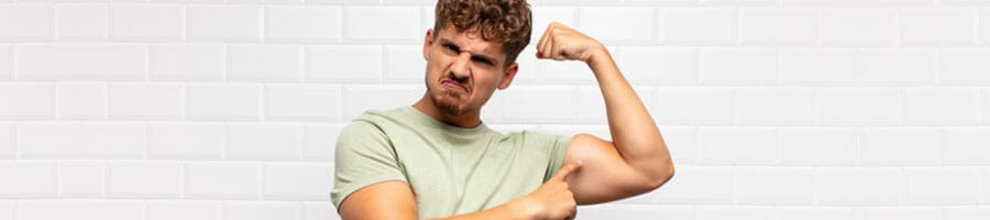 man proudly flexing his arms while pointing at it