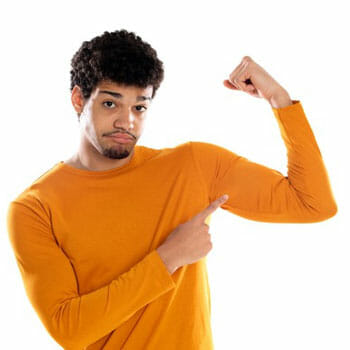 black man in a sweatshirt flexing and pointing at his biceps