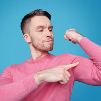 man in a sweater flexing his biceps while pointing at it