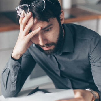 man holding his head in worry while reading a paper