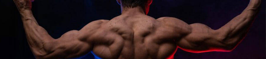 shirtless man flexing his back muscles with his arms up