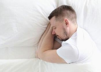 man in deep sleep laying down