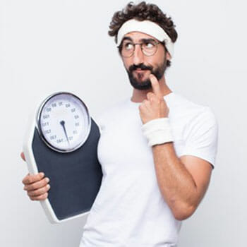 man holding a weighing scale and contemplating