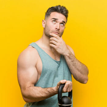 man with a thinking expression while holding a kettlebell