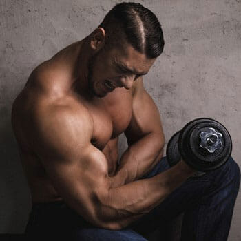 shirtless man working out with a dumbbell