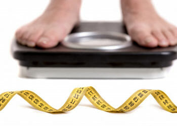 man in a weighing scale with yellow measuring tape in front