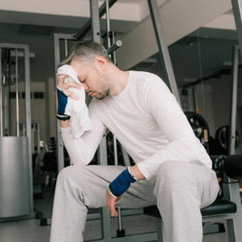 man resting in a gym while wiping sweat