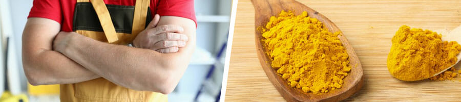 man with his arms crossed, two spoons filled with turmeric powder