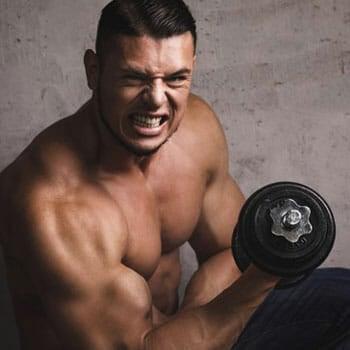 shirtless man doing a dumbbell workout