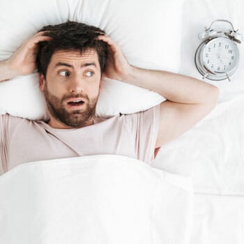 man laying down in bed in panic with his alarm clock beside