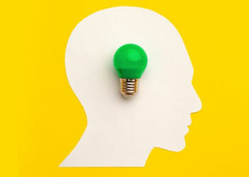 white silhouette of a head and a green light bulb on it