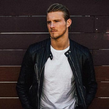 Alexander Ludwig wearing a white shirt and a leather jacket