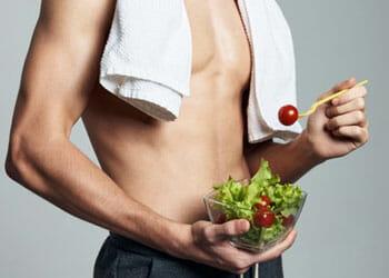 man eating a salad bowl shirtless