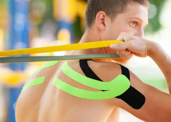 man working out with kinesio tapes on his back