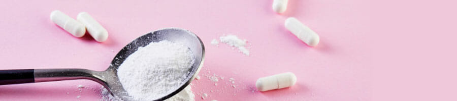 spoon filled with white powder and white pills scattered