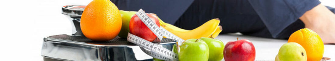 fruits and measuring tape on a weighing scale