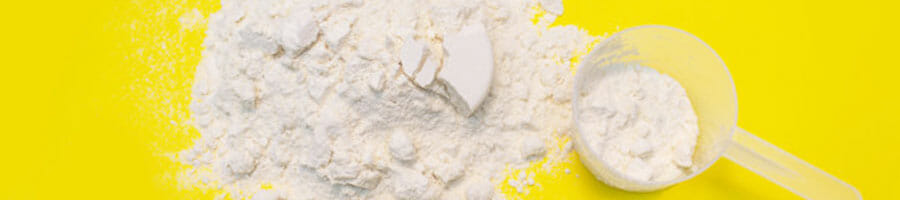 close up image of a protein scattered protein powder with a scooper