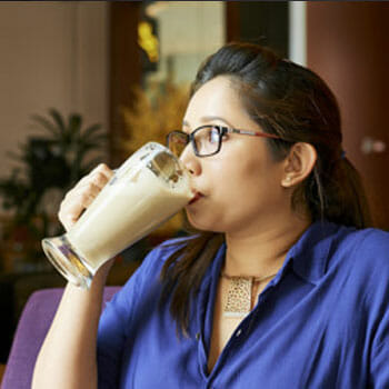 woman chugging a large glass of protein shake
