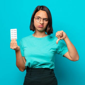 woman holding a sheet of pills with her thumbs down