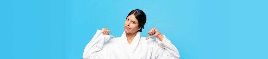 woman in a bath robe raising a thumbs down
