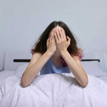 woman sitting on bed cover her face