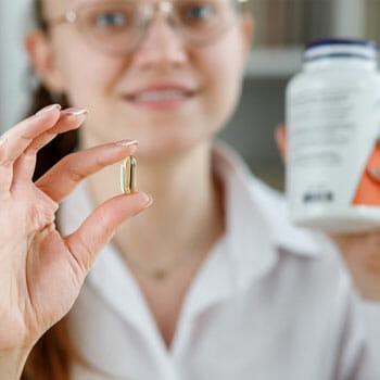 woman showing a capsule on her hand
