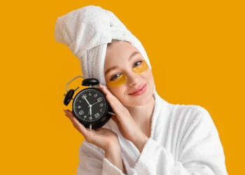 woman in a bath robe while holding a bed side clock