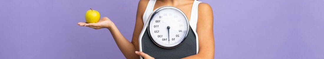 woman holding up an apple and a weighing scale