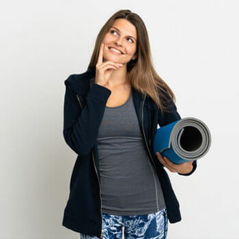 woman in yoga clothes thinking while holding a yoga mat