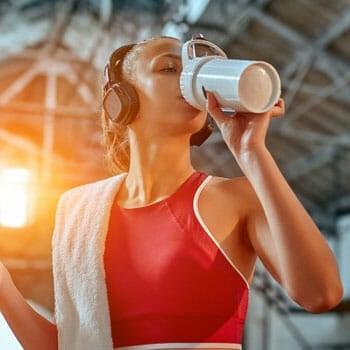 woman chugging a jug after workout
