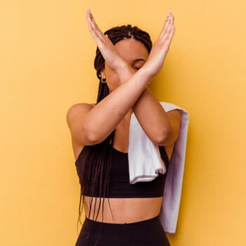 woman signing no with her arms while in gym clothes