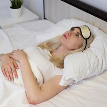 woman facing the ceiling while laying down awake