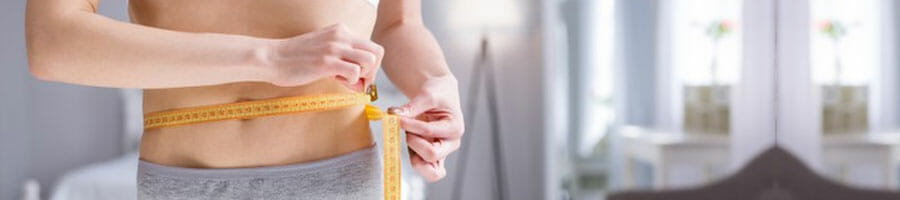 woman using a measuring tape on her waist
