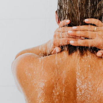 woman showing her back while taking a shower
