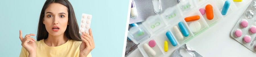 woman raising up a sachet of vitamins thinking, medicine kit