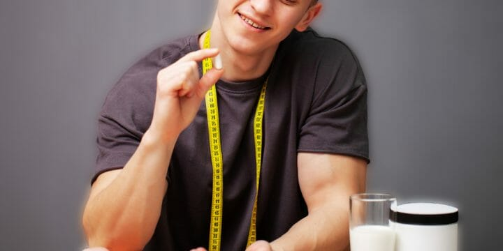 A person holding a supplement and a hanging tape maeasure