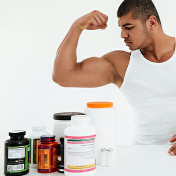 Different multivitamins and an athlete flexing his mucles