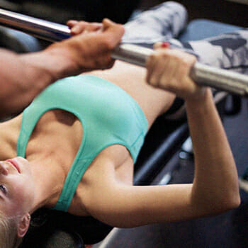 Doing a barbell bench press with a spotter